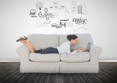 Cheerful businesswoman lying on couch and using her laptop to brainstorm photo