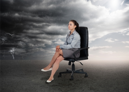 Businesswoman sitting in middle of opposite weather settings in a swivel chair Stock Photo - 20632647