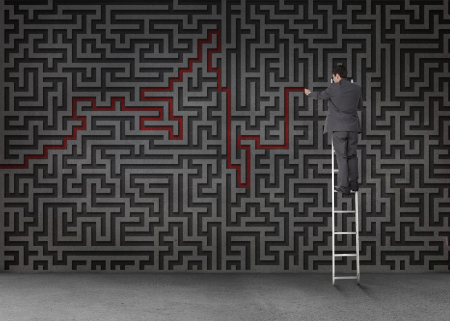 Businessman standing on a ladder and drawing a red line through black maze on a wall photo