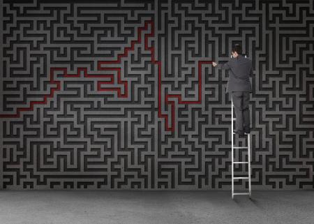 resolving: Imprenditore in piedi su una scala e tracciando una linea rossa attraverso il labirinto nero su una parete