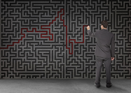 Rear view of a businessman drawing a red line through black maze on wall photo