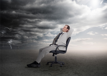 Attractive businessman sitting on a swivel chair in the desert Stock Photo - 20625408
