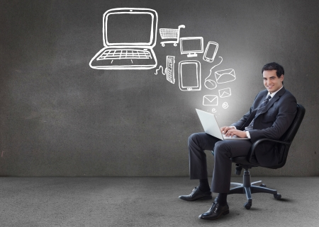 clouding: Businessman typing on his laptop with media device graphics coming from it in grey empty room Stock Photo
