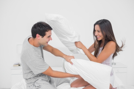 Pillow fight: Couple fighting together with pillows in bed