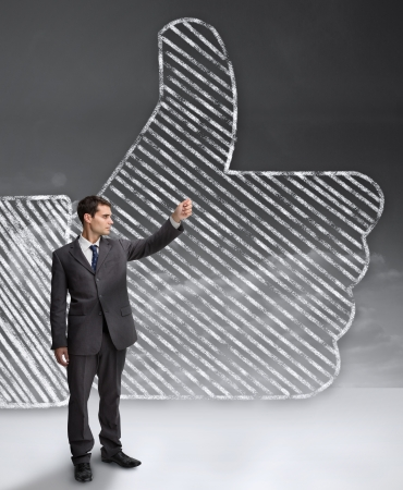 Businessman standing in front of a giant thumb up from the social network photo