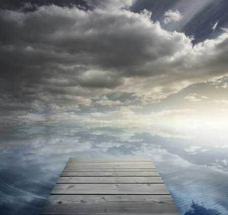 Wooden bridge leading to horizon in cloudy sky setting Stock Photo - 20625319