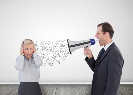 Businessman holding a megaphone and screaming at his colleague photo