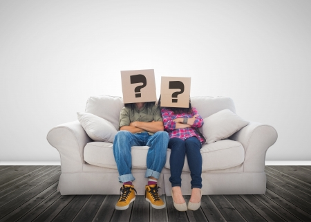 Funny couple wearing boxes with question mark on their head on a couch photo
