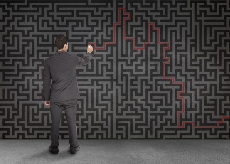 Rear view of a businessman writing a red line through black maze on a wall photo