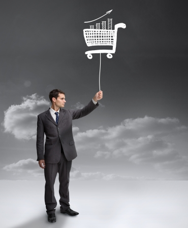 Businessman holding a floating shopping cart with clouds on the background photo