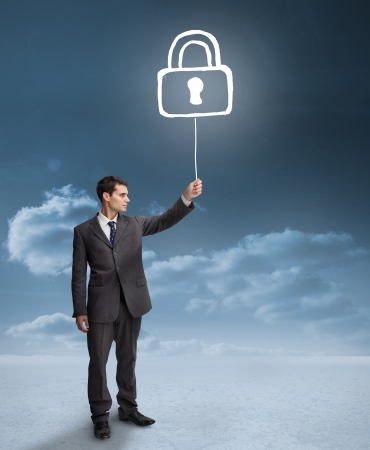 Businessman holding a floating padlock with clouds on the background photo