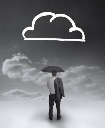 Businessman under an umbrella looking at a drawing of a cloud photo