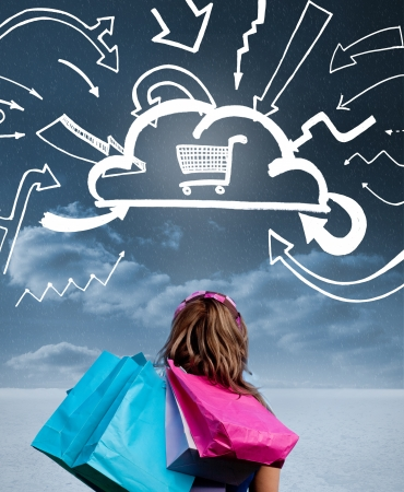 Woman with shopping bags and looking at a drawing with shopping cart into a cloud photo