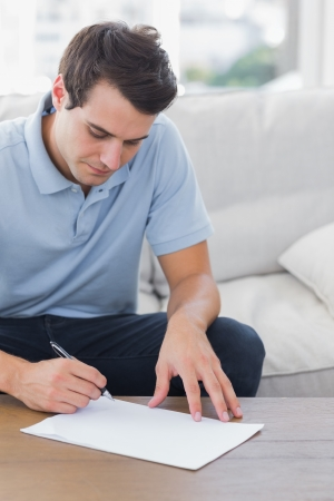 he: Man writing on a paper while he is sat on a couch in the living room