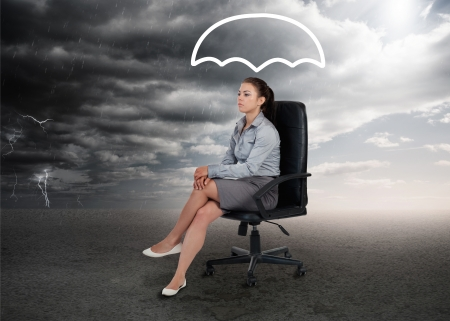 Umbrella graphic above the head of a businesswoman in stormy weather setting photo