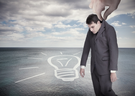 Giant hand dropping off a businessman on a surface with a drawing of a light bulb photo