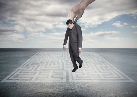 Big hand dropping off a businessman on a surface with a labyrinth drawn on it Stock Photo - 20630716