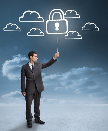Businessman holding a floating padlock around clouds on the background photo