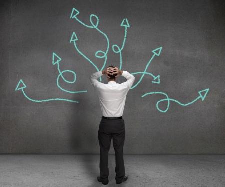 toma de decision: Destac� el empresario mirando flechas dibujado en una pared
