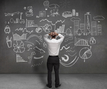 toma de decision: Destac� el empresario mirando los dibujos de cuadros y bocetos en una pared