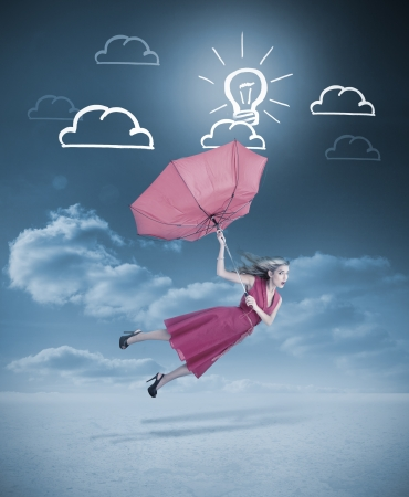 Glamour woman flying with a red umbrella under drawings of clouds and light bulb photo