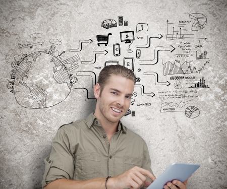 graphic tablet: Attractive man using a tablet computer with sketches on the background