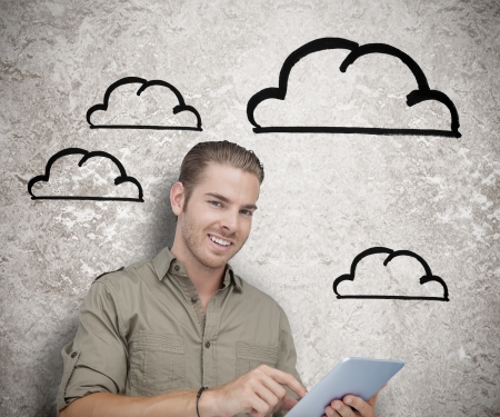 Smiling man using a tablet computer with drawings of clouds on the background photo
