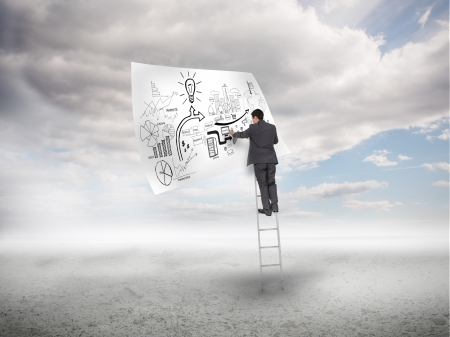 Businessman on a ladder sketching on a paper with blue sky on the background photo