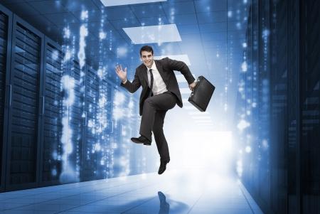 Businessman jumping in a data center corridor Stock Photo - 20625030