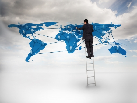 businessman standing: Businessman standing on a ladder drawing a world map with blue sky on the background Stock Photo