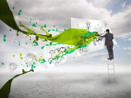 Businessman drawing on a paper next to green paint splash with blue sky on the background photo