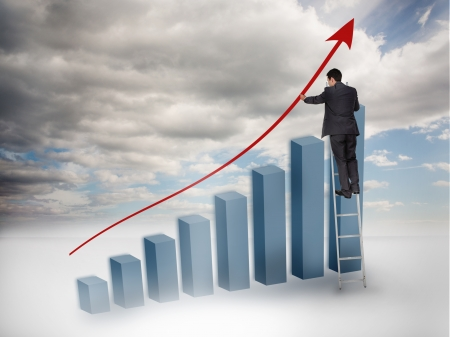 Businessman drawing a red arrow over a growing chart with blue sky on the background photo