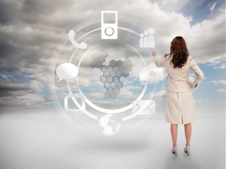 Businesswoman touching at a hologram with icons and blue sky on the background photo