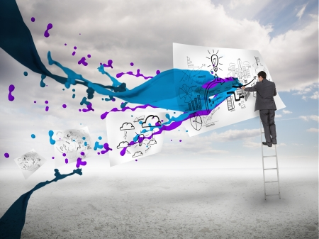 Businessman drawing on a paper next to paints splash with blue sky on the background photo