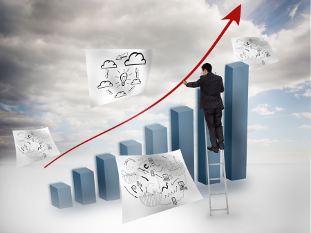 Businessman drawing a red arrow over a chart with blue sky on the background photo