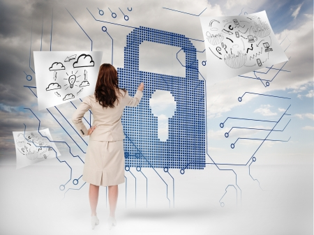 Businesswoman selecting a giant padlock with drawings floating on a blue sky background photo