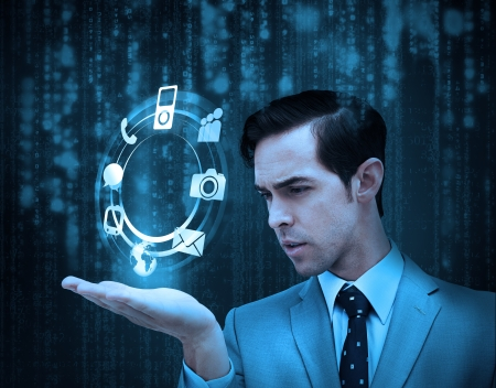 Businessman holding a hologram with smartphone applications with matrix on the background photo