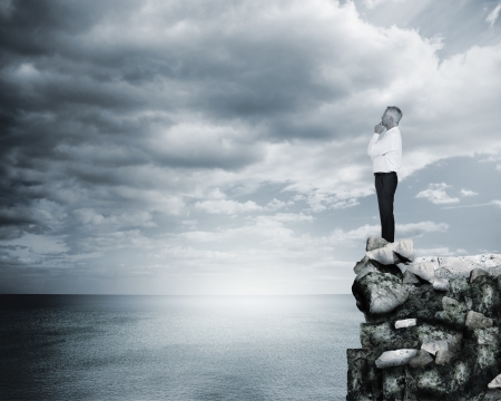 Thoughtful businessman standing at the edge of a cliff with the sea on the background photo