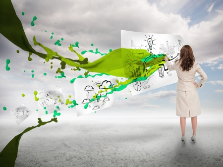 Creative businesswoman drawing on a paper next to paint splash with blue sky on the background photo