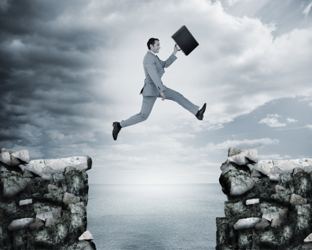 risk taking: Businessman jumping a gap between cliffs with the sea on the background Stock Photo