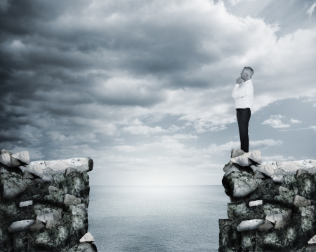 cliff edge: Businessman thinking at the edge of a cliff with the sea on the background Stock Photo