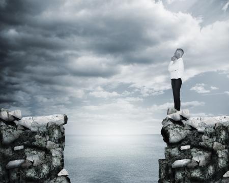 Zakenman denken aan de rand van een klif met de zee op de achtergrond