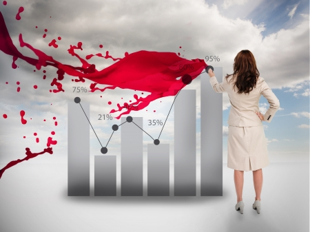 Creative businesswoman drawing a chart next to red paint splash and blue sky on the background photo
