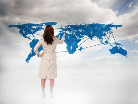 INTERNATIONAL BUSINESS: Empresaria tocando en un mapa del mundo con el cielo azul en el fondo