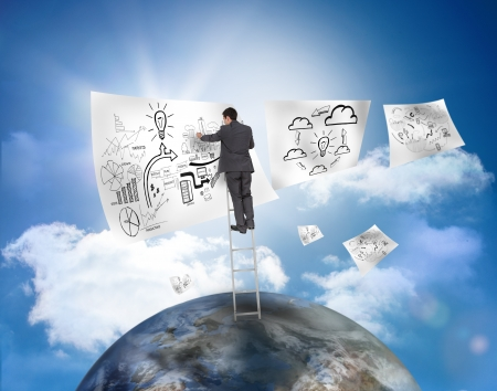 Businessman on a ladder over a planet drawing on a paper with blue sky on the background photo