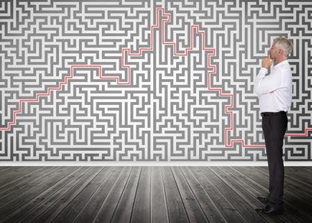 dudando: Hombre de negocios pensativo de pie y mirando a un laberinto en una pared