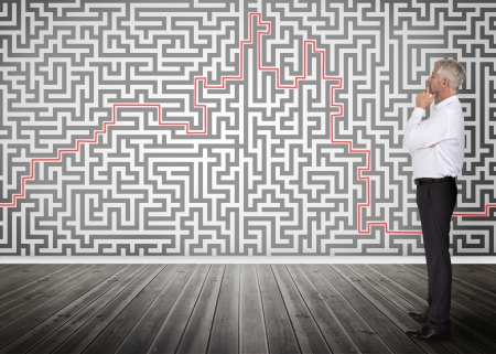 hesitating: Thoughtful businessman standing and looking at a maze on a wall