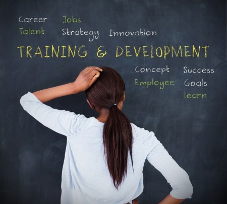 training and development: Attractive woman looking at a chalkboard with business terms written on it