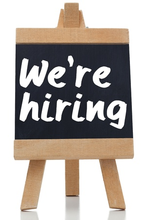 recruit: We are hiring written with a chalk on blackboard against white background