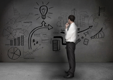 Businessman looking at a wall with drawings of chart and light bulb  photo